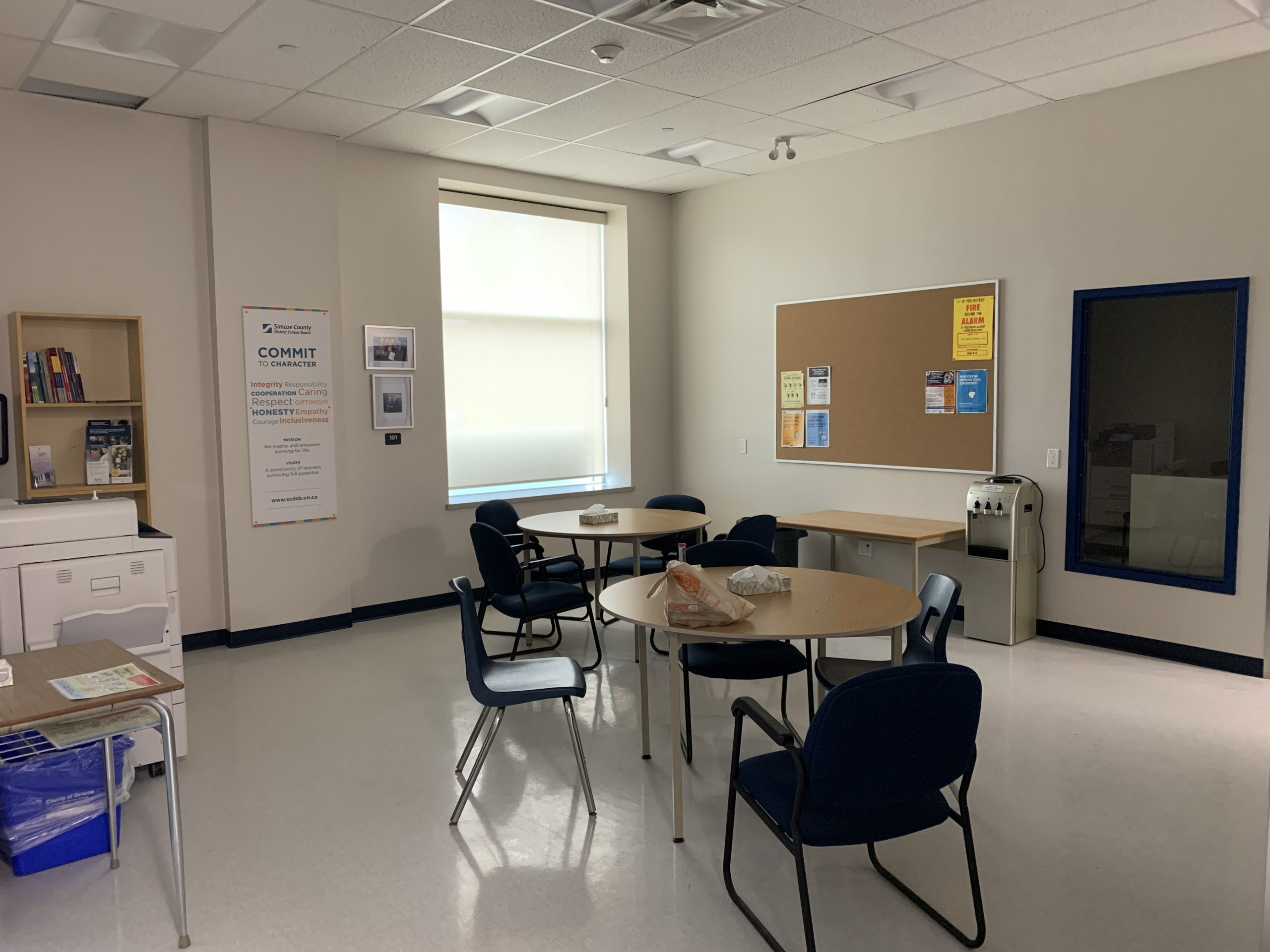 The common area, with circle tables and blue chairs at the Simcoe County District School Board's North Simcoe Learning Centre and Simcoe Shores Secondary School – Midland Campus. This project was managed by our Employee Spotlight feature, Jana Shneider.
