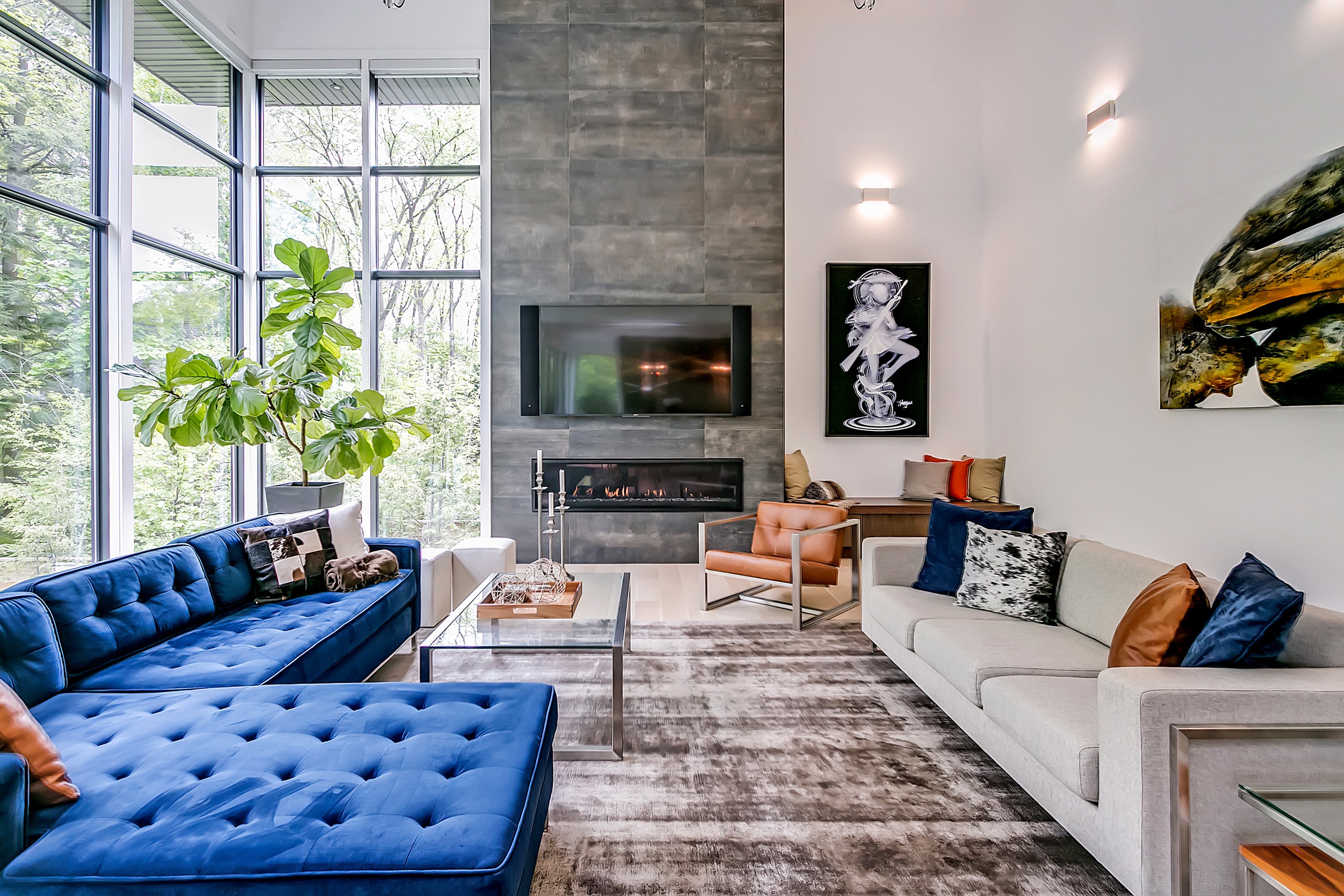 A living space with the fireplace in the center with a tv. There are two couches: a blue sectional on the left and a grey couch on the left.