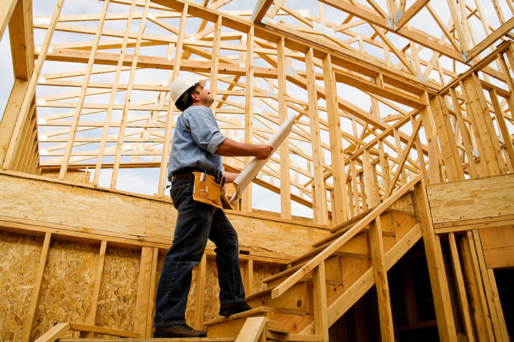 A home builder/contractor (a man) on stairs in a home's framing stage.