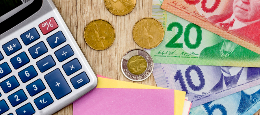 Canadian currency (three loonies, a toonie, a $5, $10, $20 and $50 bill), next to a calculator.